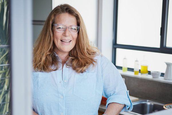 Cookbook Author Adeena Sussman in her kitchen chopping vegetables.