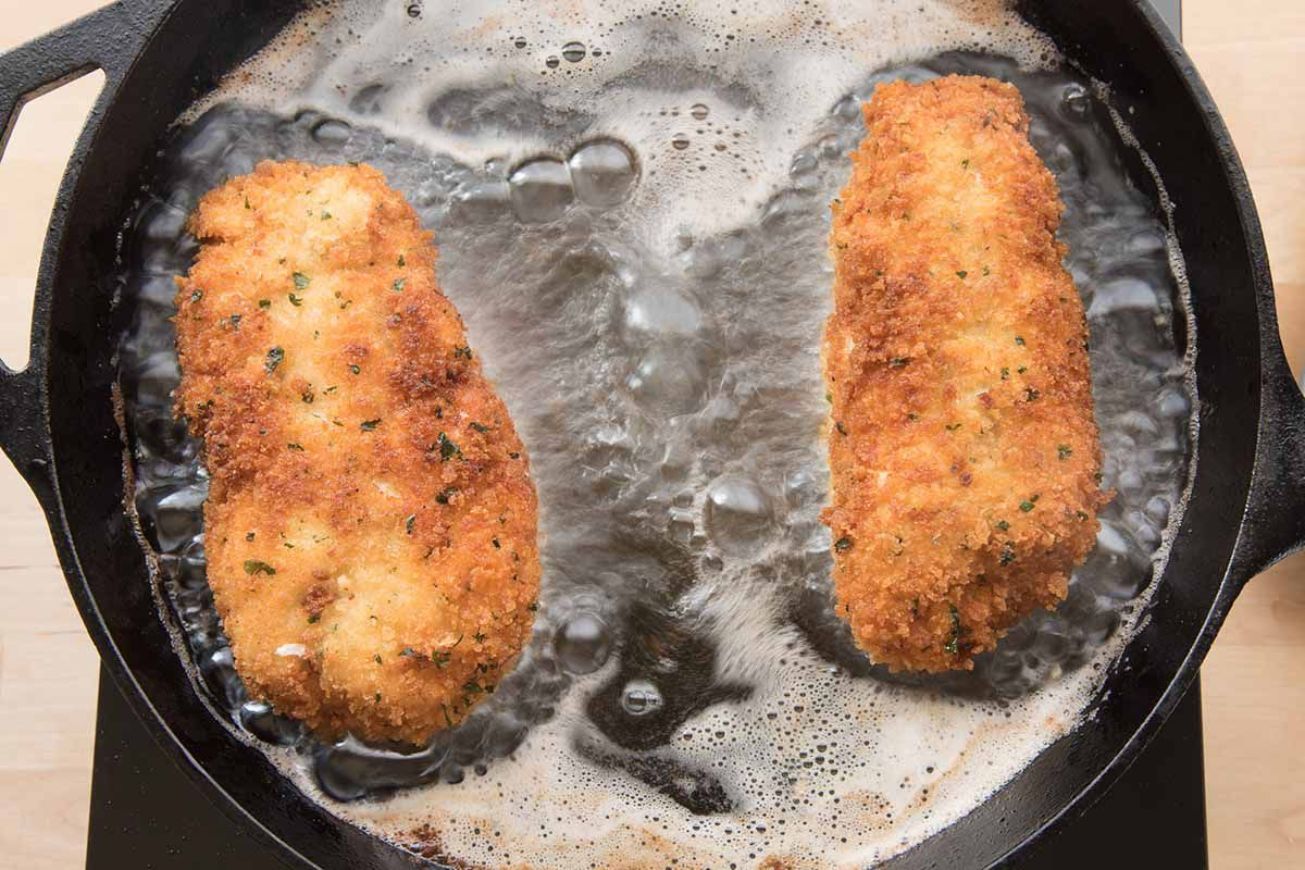 Easy Chicken Crodon Bleu being fried in butter in a black cast iron skillet.