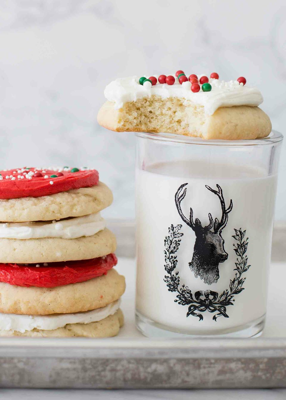 Homemade sugar cookies stacked and set next to a glass of milk.
