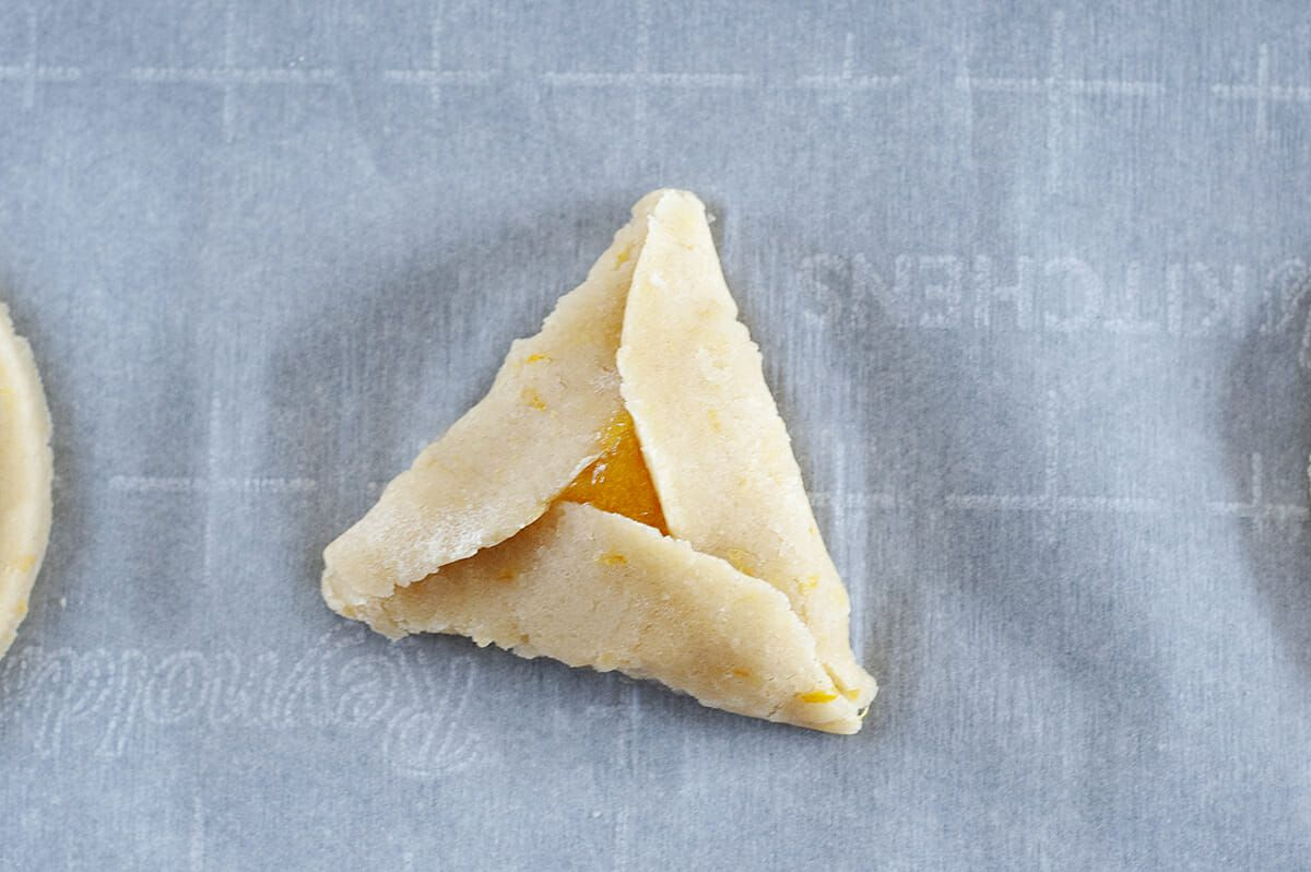 Unbaked apricot hamantaschen on a gridded parchment paper.