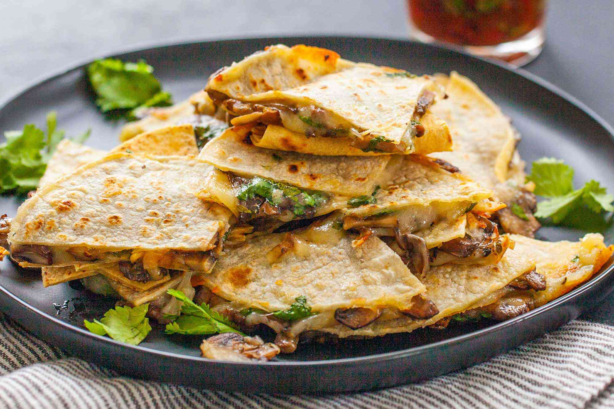 Vegetarian Quesadilla Recipe -close up of cheese and mushroom quesadillas stacked on top of each other with a jar of red salsa in the background.