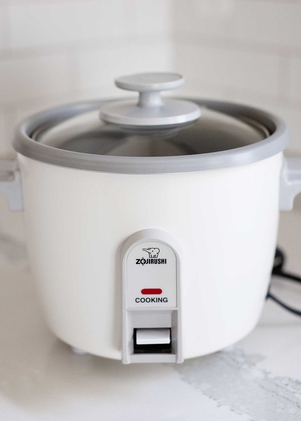 Side view of a Zojirushi rice cooker on a white countertop.