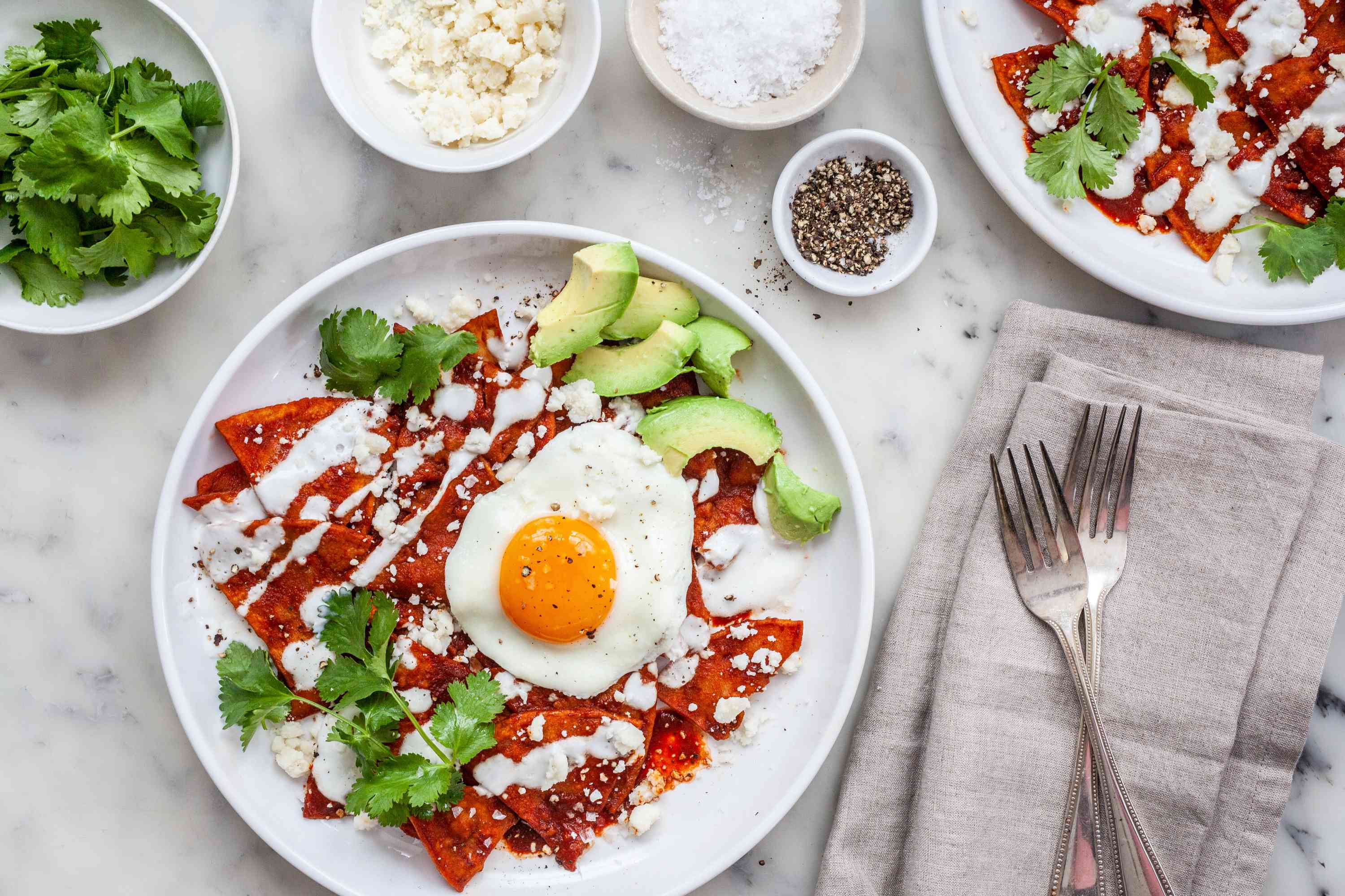 Chilaquiles on a plate with extra toppings around the plate.