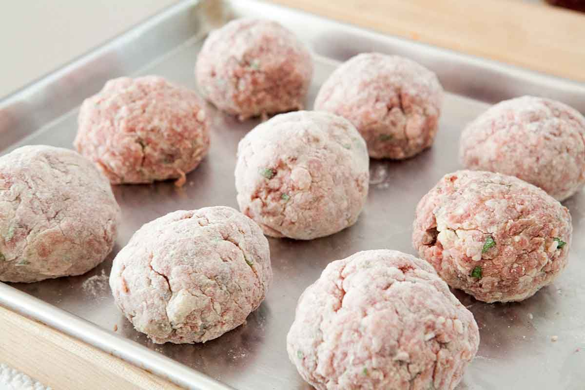 Coat homemade italian meatballs in flour