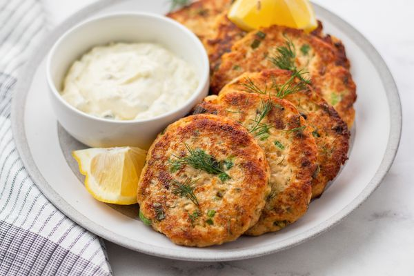 Salmon patties set on a plate with a dip and lemon.