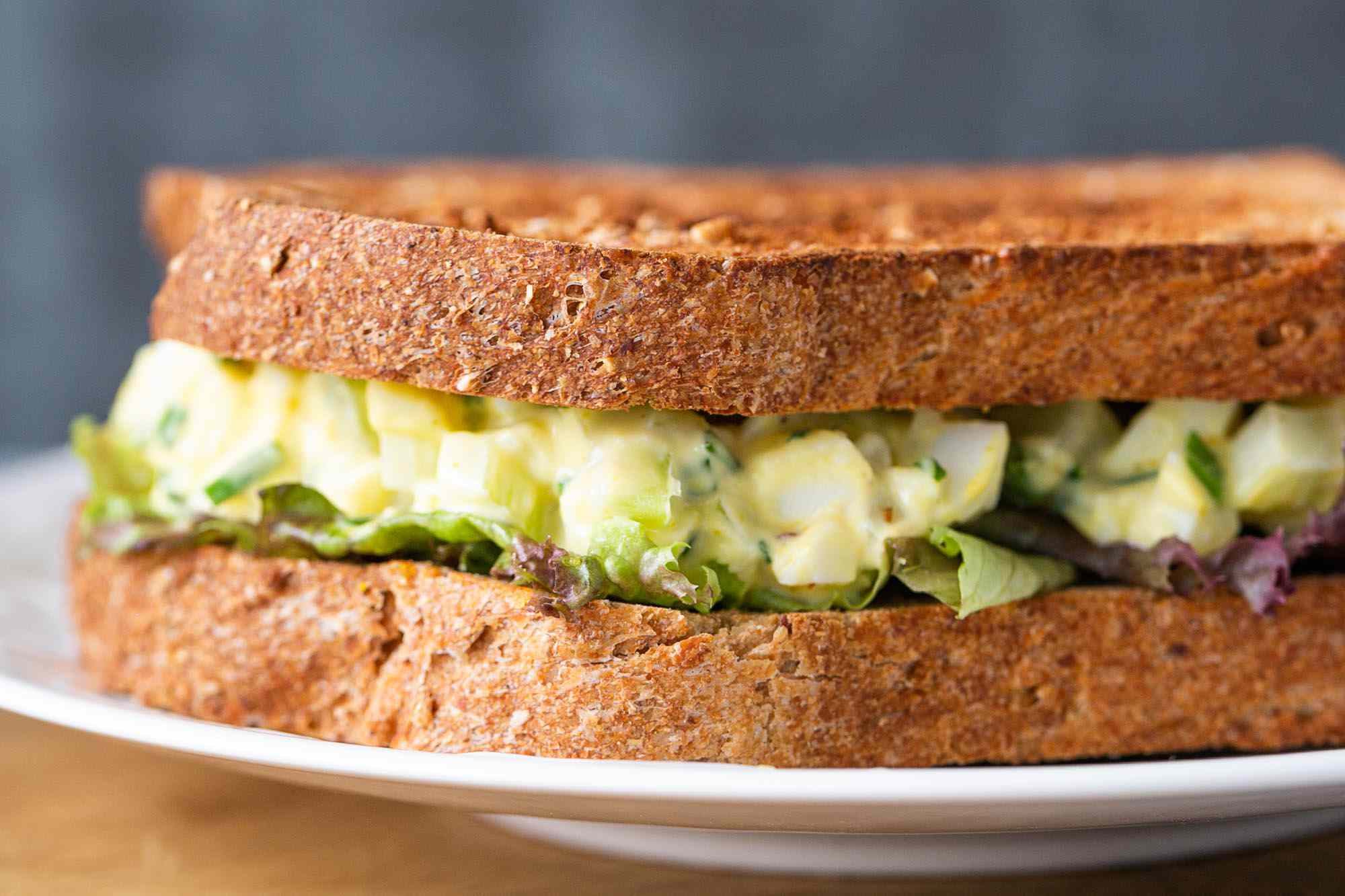 Homemade egg salad sandwich on a plate with a leaf of lettuce