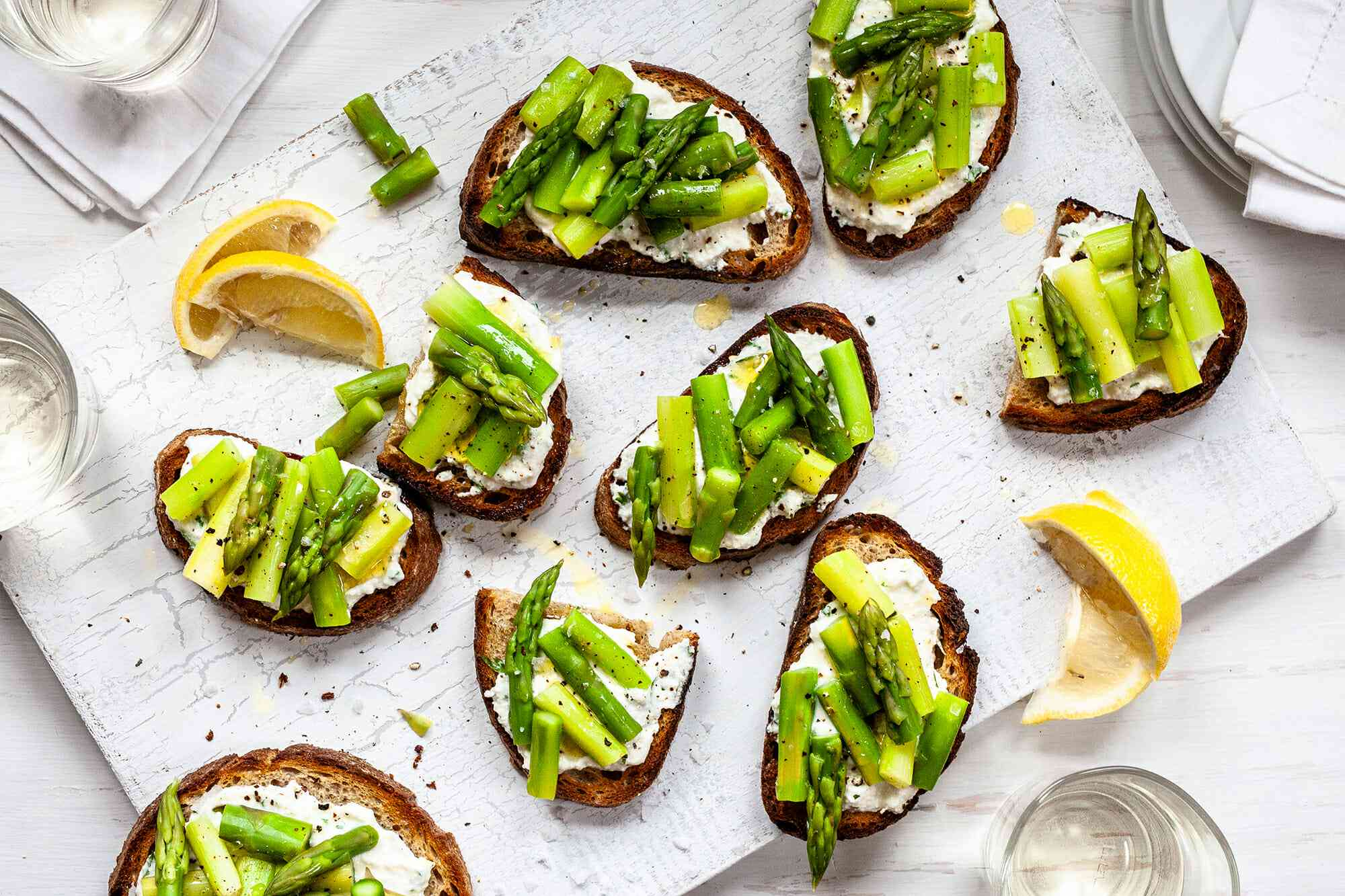 Crostini Recipe with Asparagus - many bruschetta with asparagus and ricotta on a white background with lemon wedges