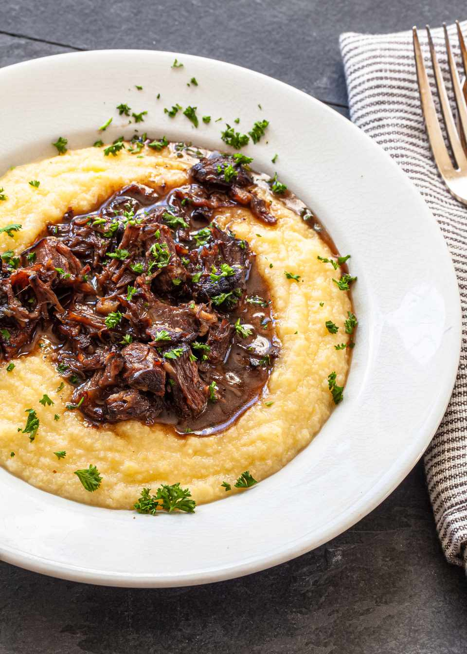 A bowl of grits and braised oxtails.