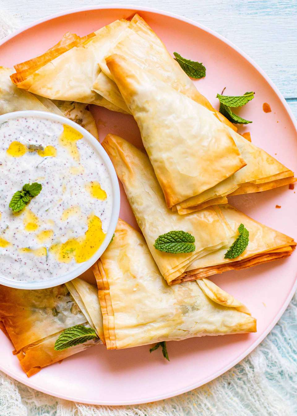 Baked Chicken Samosa folded into a triangle with Mint Yogurt Dip on a pink plate