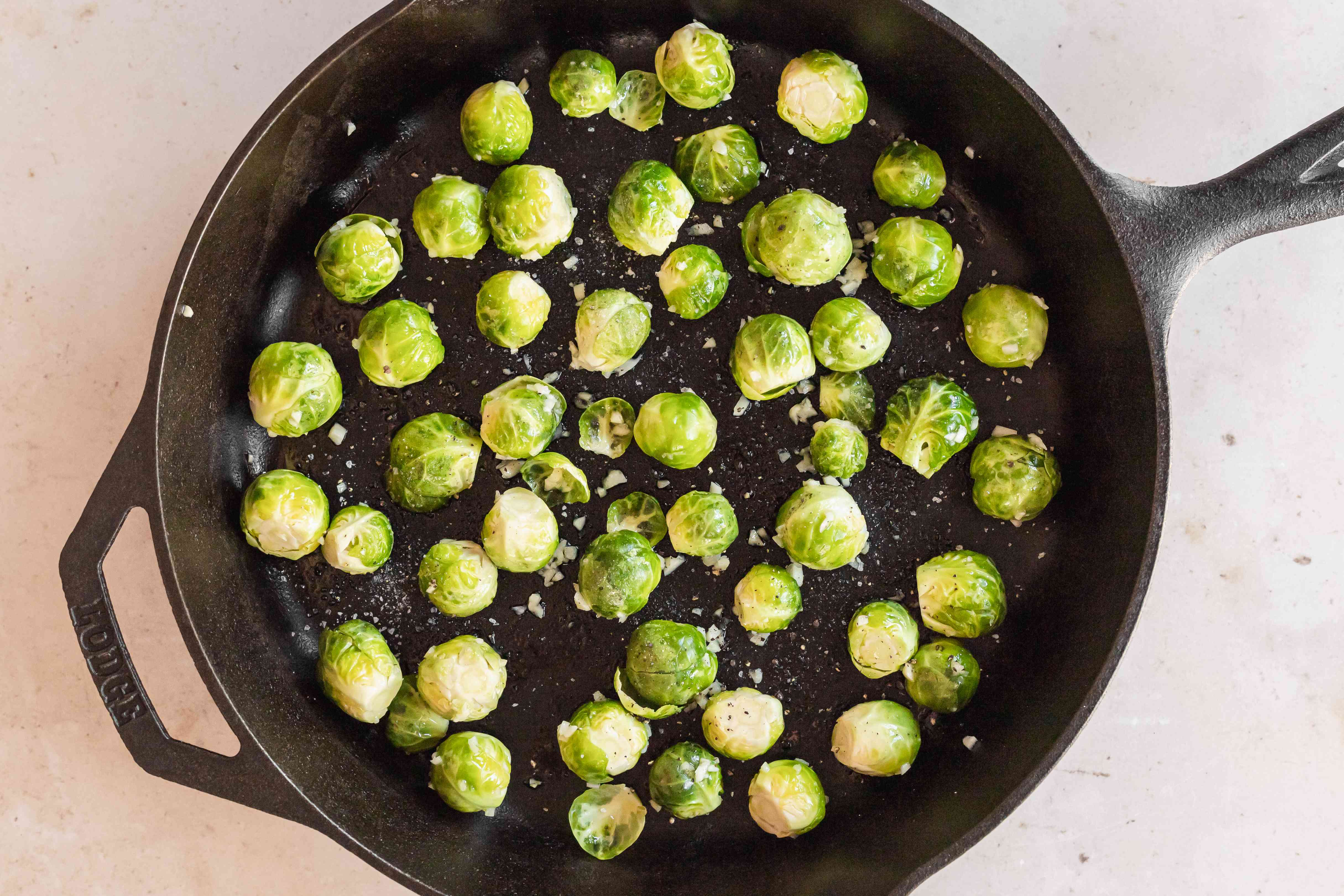 Overhead view of a cast iron skillet to show how to roast brussel sprouts.